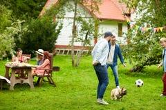 踢与狗的朋友橄榄球在夏天庭院 免版税库存照片