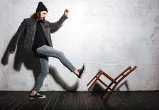 踢与脚的一个有胡子的行家人的画象椅子 库存照片