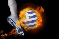 踢发火焰乌拉圭球的足球运动员 免版税图库摄影