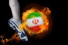 踢发火焰伊朗球的足球运动员 免版税库存图片