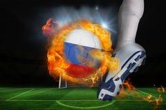 踢发火焰俄罗斯旗子球的足球运动员 库存照片