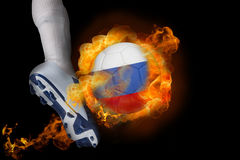 踢发火焰俄罗斯球的足球运动员 库存图片