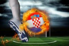 踢发火焰克罗地亚旗子球的足球运动员 免版税库存图片