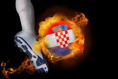 踢发火焰克罗地亚球的足球运动员 库存照片