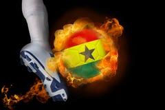 踢发火焰加纳旗子球的足球运动员 库存照片
