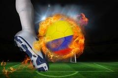 踢发火焰哥伦比亚旗子球的足球运动员 库存照片