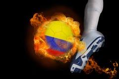 踢发火焰哥伦比亚球的足球运动员 免版税图库摄影