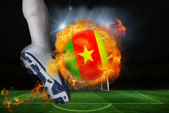 踢发火焰喀麦隆旗子球的足球运动员 库存照片