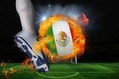 踢发火焰墨西哥旗子球的足球运动员 免版税库存图片