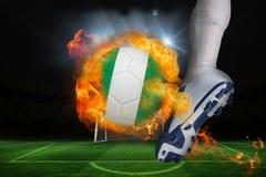 踢发火焰尼日利亚旗子球的足球运动员 免版税库存图片