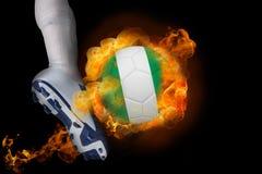 踢发火焰尼日利亚球的足球运动员 图库摄影