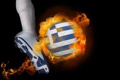 踢发火焰希腊旗子球的足球运动员 库存照片