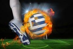 踢发火焰希腊旗子球的足球运动员 图库摄影