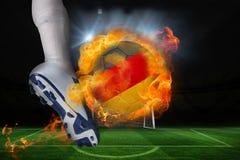 踢发火焰德国旗子球的足球运动员 免版税库存照片