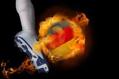 踢发火焰德国球的足球运动员 库存照片