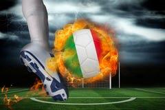 踢发火焰意大利旗子球的足球运动员 免版税库存图片