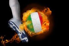 踢发火焰意大利球的足球运动员 图库摄影