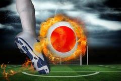 踢发火焰日本旗子球的足球运动员 库存图片