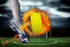 踢发火焰比利时旗子球的足球运动员 免版税图库摄影