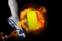 踢发火焰比利时球的足球运动员 免版税库存图片
