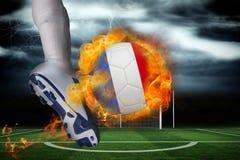踢发火焰法国旗子球的足球运动员 图库摄影