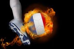 踢发火焰法国球的足球运动员 免版税库存照片