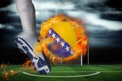 踢发火焰波斯尼亚旗子球的足球运动员 免版税图库摄影