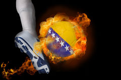 踢发火焰波斯尼亚球的足球运动员 免版税图库摄影