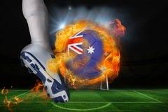 踢发火焰澳大利亚旗子球的足球运动员 免版税库存照片