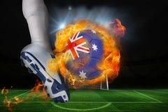 踢发火焰澳大利亚旗子球的足球运动员 免版税图库摄影