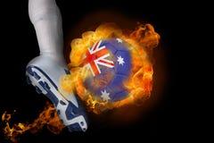 踢发火焰澳大利亚球的足球运动员 免版税库存照片