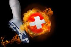踢发火焰瑞士球的足球运动员 库存图片