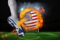 踢发火焰美国旗子球的足球运动员 免版税库存图片