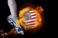 踢发火焰美国球的足球运动员 免版税库存照片