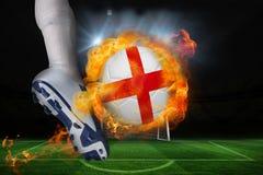 踢发火焰英国旗子球的足球运动员 免版税库存照片