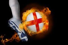 踢发火焰英国球的足球运动员 免版税库存图片