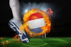 踢发火焰荷兰旗子球的足球运动员 免版税库存图片