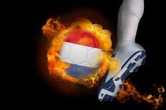 踢发火焰荷兰球的足球运动员 库存照片
