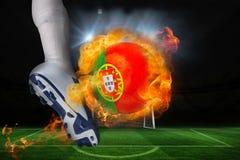 踢发火焰葡萄牙旗子球的足球运动员 免版税库存照片