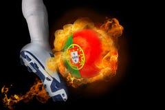 踢发火焰葡萄牙球的足球运动员 库存照片