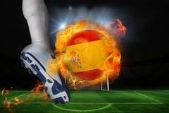 踢发火焰西班牙旗子球的足球运动员 免版税库存照片