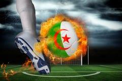 踢发火焰阿尔及利亚旗子球的足球运动员 库存图片