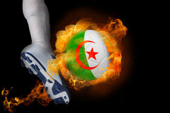 踢发火焰阿尔及利亚球的足球运动员 库存图片