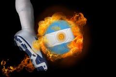 踢发火焰阿根廷旗子球的足球运动员 免版税库存图片