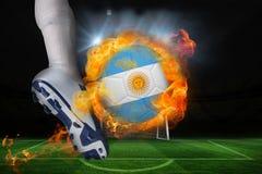 踢发火焰阿根廷旗子球的足球运动员 免版税库存照片