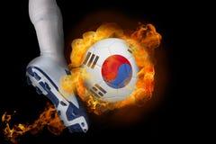 踢发火焰韩国共和国球的足球运动员 免版税库存图片