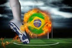 踢发火焰巴西旗子球的足球运动员 库存图片