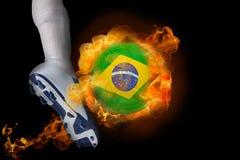 踢发火焰巴西球的足球运动员 库存图片