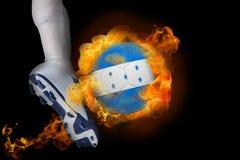 踢发火焰洪都拉斯旗子球的足球运动员 免版税库存照片