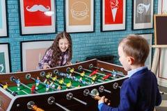 踢在一个咖啡馆的滑稽的孩子桌橄榄球在情人节 库存图片